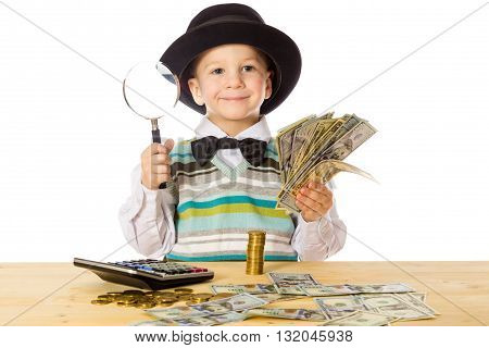 Smiling little boy in black hat counting money on the table, isolated on white
