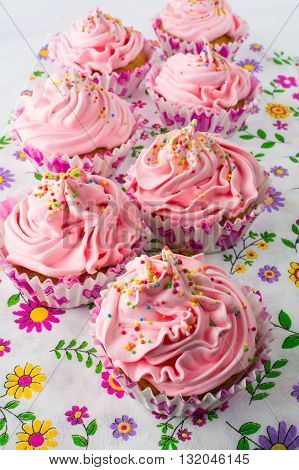 Pink cupcakes on floral pattern napkin. Homemade cupcake. Sweet dessert. Sweet pastry. Gourmet cupcakes. Sweet cupcake. Birthday cupcakes.