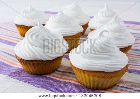 White cupcakes on the striped linen napkin. Birthday cupcakes. Homemade cupcake. Sweet cupcake. Gourmet cupcakes. Sweet pastry. Sweet dessert.