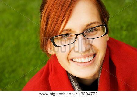 Beautiful young redhead woman relaxing outdoors