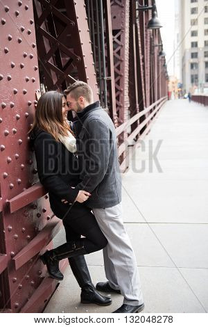 A gorgeous young millennial caucasian couple posing in Chicago on a cold day outside with the background of the city.