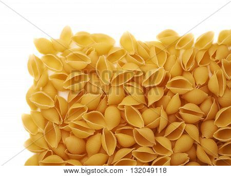 Pile of dry conchiglie yellow pasta over isolated white background