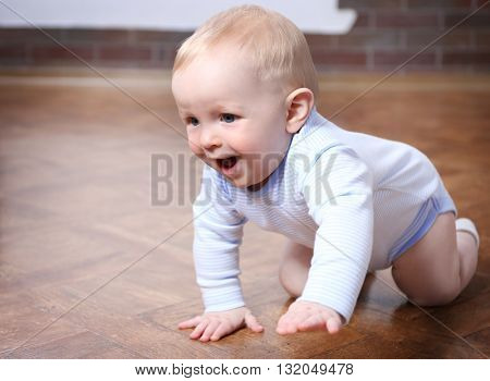 Crawling baby on the wooden floor in the room