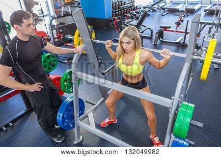 man and blonde woman with barbell training muscles in gym. woman and personal trainer in gym