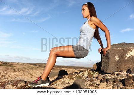Strength training fitness woman working out arms muscles doing triceps dips. Asian athlete exercising with bodyweight exercises for toned body. Sun suntan skincare in summer desert landscape.
