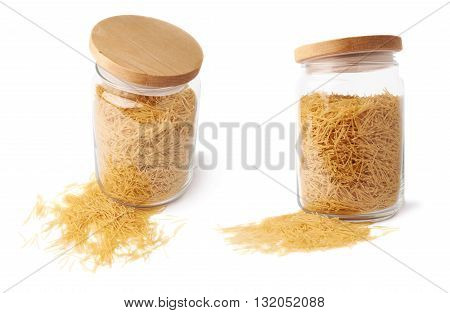 Set of glass jar filled with dry noodles yellow pasta over isolated white background, different foreshortenings