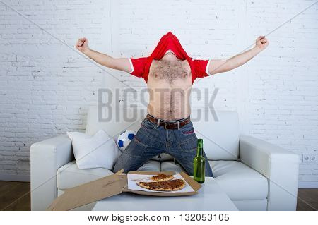 young man watching football game on television celebrating goal crazy with jersey on his head jumping on sofa couch at home with ball holding beer bottle eating pizza excited