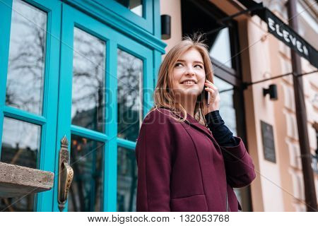 Cheerful cute young woman walking in the city and talking on cell phone