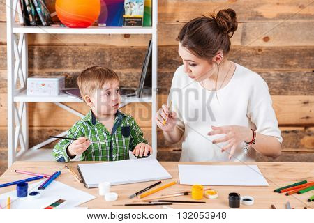 Pretty young mother and his cute little son painting and talking together
