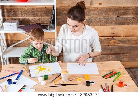 Mother and little son painting sun with yellow paint together