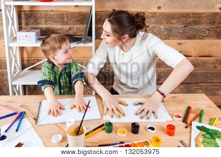 Cheerful little boy and his mother making prints of painted hands in colorful paint on the paper