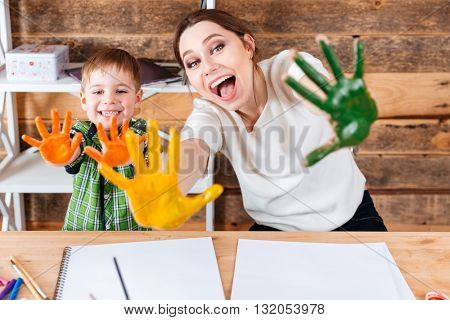 Happy excited mother and her little son showing painted hands in colorful paint