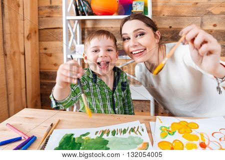 Cheerful little boy and his mother painting and showing paintbrushes to camera together