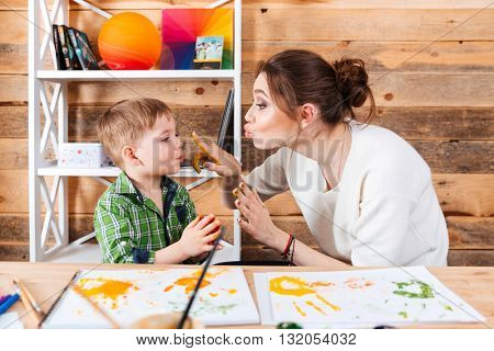 Happy mother touching face of her little son with hands painted in colorful paints and having fun together