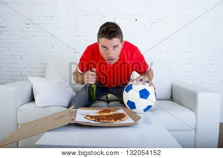 young man alone holding ball and beer bottle in stress wearing team jersey watching football game on television at home living room sofa couch with pizza box excited and in disbelief face expression
