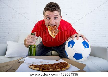 young man watching football game on television looking excited and anxious sitting on sofa couch at home holding ball beer and beer bottle eating pizza hanging from his mouth