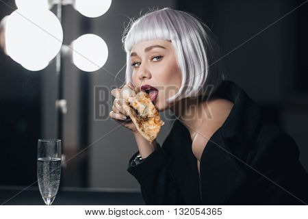 Seductive pretty young woman eating pizza and drinking champagne in dressing room