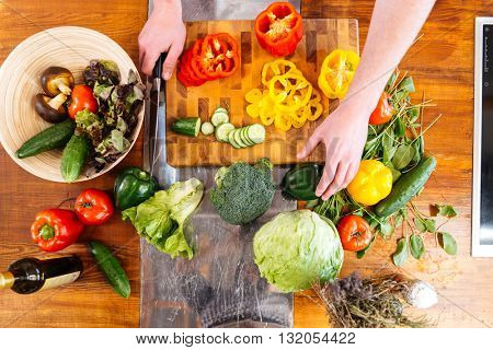 Top view of hands of young man cutting fresh vegetables on wooden table
