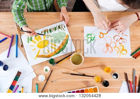 Top view of hands of mother and son painting bright colorful pictures using watercolor paints