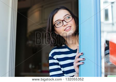 Happy beautiful young woman in glasses looking out of cafe