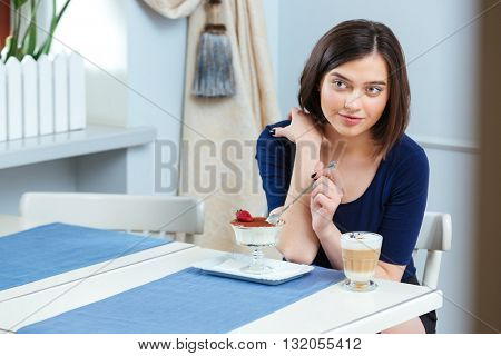 Portrait of beautiful young woman eating dessert and drinking coffee latte in cafe