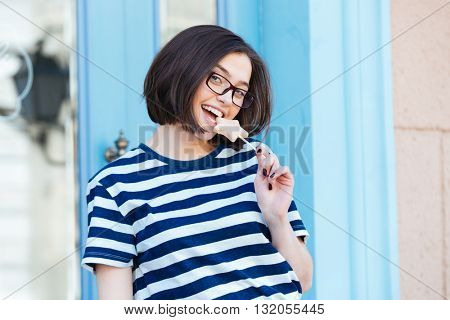 Cheerful attractive young woman in glasses eating star shaped lollipop