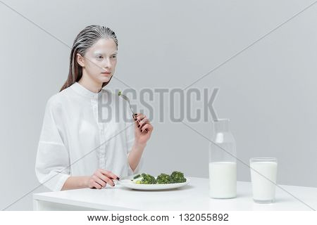 Beautiful fashion woman having lunch at the table using knife and fork over gray background