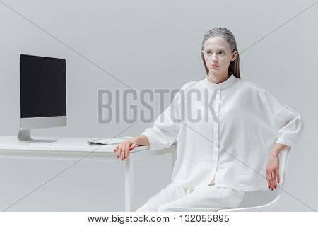 Beautiful fashion girl sitting at the table with computer, pc over gray background