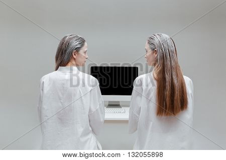 Two fashion women looking at each other at the computer over gray background