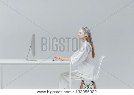 Cosmic fashion woman sitting at the table with computer, pc over gray background