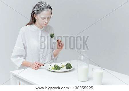 Fashion beautiful woman eating healthy food at the table using fork and knife over gray background