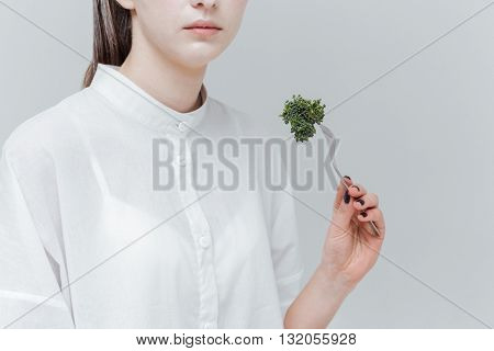 Cropped image of stylish beautiful girl eating with fork over gray background