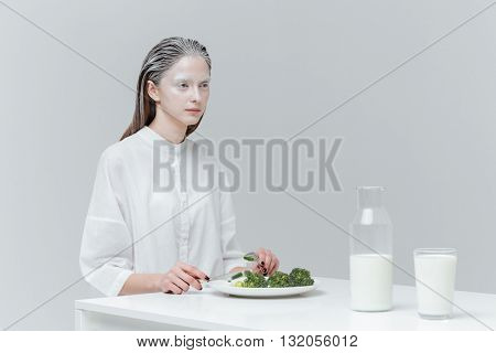 Beautifil unusual woman having healthy lunch at the table over gray background