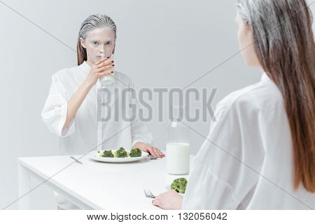 Two fashion beautiful girls having lunch at the table over gray background