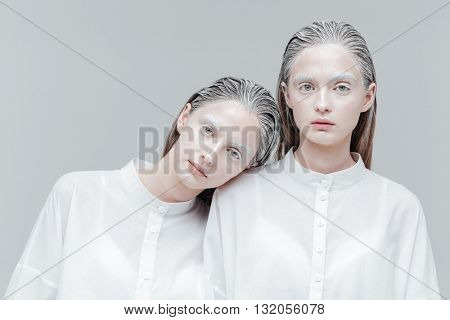 Close-up portrait of two beautiful mystical women in smart white shirts over gray background