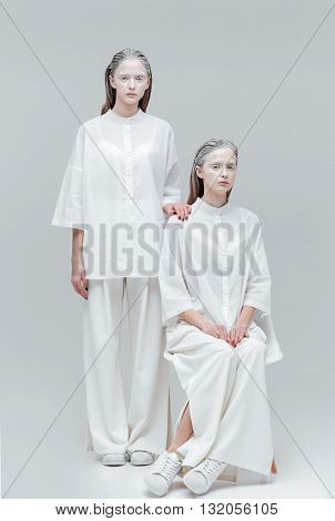 Two beautiful fashion girls wearing white clothes isolated on gray