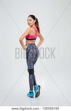 Full length portrait of a beautiful sports woman looking back at camera isolated on a white background
