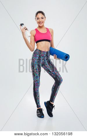 Full length portrait of a smiling woman holding yoga mat and shaker isolated on a white background