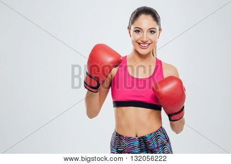 Smiling woman in boxing gloves looking at camera isolated on a white background