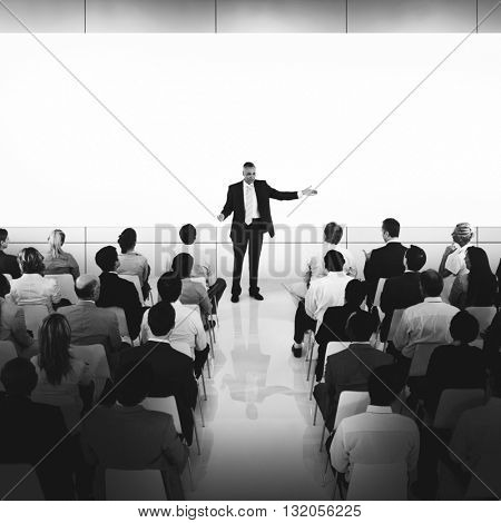 Group Of Business People In Seminar Listening To The Businessman In The Center Pointing To The Screen