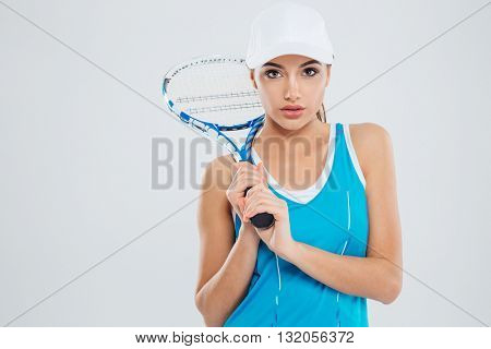 Portrait of a beautiful woman holding tennis racquet and looking at camera isolated on a white background