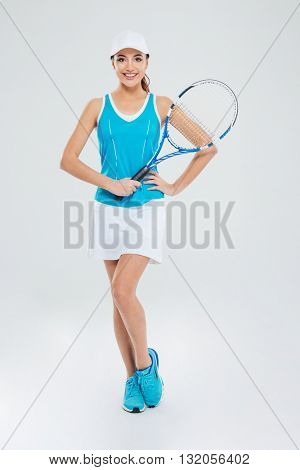Full length portrait of a happy female tennis player standing isolated on a white background and looking at camera