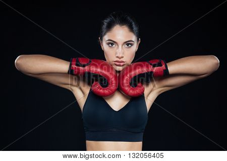 Beautiful fitness woman posing with bloxing gloves on black background