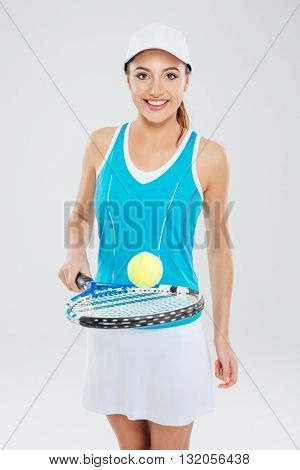 Portrait of a beautiful woman playing in tennis and looking at camera isolated on a white background