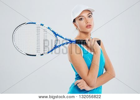 Portrait of a beautiful female tennis player looking at camera isolated on a white background