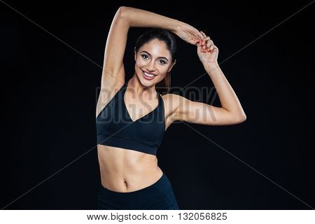 Portrait of a smiling fitness woman posing on black background