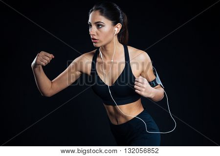 Portrait of a fitness woman training with earphones on black background