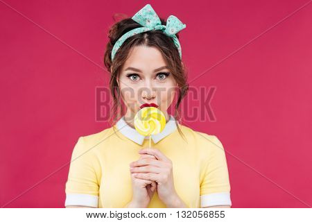 Portrait of beautiful pinup girl eating sweet yellow lollipop over pink background