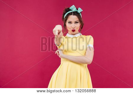 Lovely playful young woman in yellow dress standing and pointing on you over pink background
