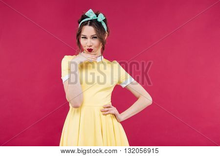Happy thoughtful pinup girl in yellow dress standing and posing over pink background